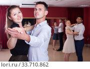 Купить «Smiling dancing couples enjoying foxtrot», фото № 33710862, снято 24 мая 2017 г. (c) Яков Филимонов / Фотобанк Лори