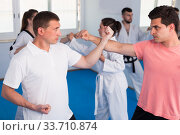 Adult males and females are practicing new karate moves in pairs. Стоковое фото, фотограф Яков Филимонов / Фотобанк Лори
