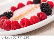 Купить «raspberries and blackberries laid out on a white plate in circle with yogurt and cinnamon», фото № 33711290, снято 2 июня 2019 г. (c) Татьяна Яцевич / Фотобанк Лори