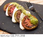 caprese salad with mozzarella, black tomatoes and pesto on black stone plate. Стоковое фото, фотограф Татьяна Яцевич / Фотобанк Лори
