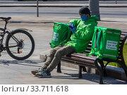 Курьер сервиса доставки еды Delivery Club принимает заказ в парке в центре города Москвы во время эпидемии коронавируса COVID-19 в Россия (2020 год). Редакционное фото, фотограф Николай Винокуров / Фотобанк Лори