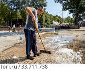 Купить «Помывка брусчатки тротуара с помощью швабры», фото № 33711738, снято 5 сентября 2019 г. (c) Вячеслав Палес / Фотобанк Лори