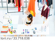 Купить «Top view of young adult fashion designer drawing and sketching her work at her atelier studio with colour palette as sole owner. Using for entrepreneur startup concept.», фото № 33718038, снято 11 июля 2020 г. (c) easy Fotostock / Фотобанк Лори