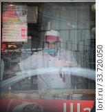 Балашиха, работник продуктовой палатки с Георгиевской лентой, в дни самоизоляции при коронавирусной инфекции COVID-19. Редакционное фото, фотограф Дмитрий Неумоин / Фотобанк Лори