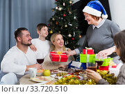 Купить «Elderly woman giving Christmas presents to family», фото № 33720510, снято 17 декабря 2017 г. (c) Яков Филимонов / Фотобанк Лори