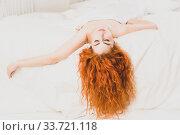 Beautiful redhaired woman lying on bed in bedroom. Стоковое фото, фотограф Дмитрий Черевко / Фотобанк Лори