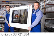 Production workers in coverall with different finished PVC profiles and windows at factory. Стоковое фото, фотограф Яков Филимонов / Фотобанк Лори