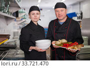 Male chef with female assistant presenting cooked dish. Стоковое фото, фотограф Яков Филимонов / Фотобанк Лори