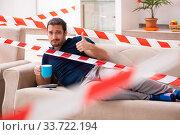 Купить «Young man feeling bored at home in self-isolation concept», фото № 33722194, снято 1 апреля 2020 г. (c) Elnur / Фотобанк Лори