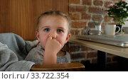Купить «Cute little girl touches nose while sitting on chair near desk with laptop at home», видеоролик № 33722354, снято 7 мая 2020 г. (c) Ekaterina Demidova / Фотобанк Лори