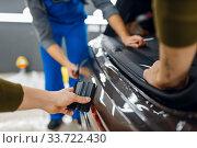 Купить «Two workers smoothes car protection film on bumper», фото № 33722430, снято 20 марта 2020 г. (c) Tryapitsyn Sergiy / Фотобанк Лори