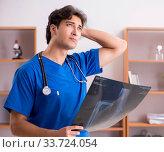 Купить «Young handsome doctor working in the hospital», фото № 33724054, снято 10 августа 2018 г. (c) Elnur / Фотобанк Лори