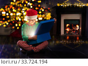 Boy open present near New Year tree and fireplace. Стоковое фото, фотограф Сергей Новиков / Фотобанк Лори