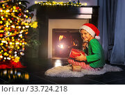 Boy with present and Christmas tree near fireplace. Стоковое фото, фотограф Сергей Новиков / Фотобанк Лори
