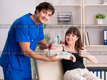 Young woman with bandaged arm visiting male doctor traumotologis