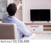 Купить «Young man watching tv at home», фото № 33726498, снято 9 марта 2018 г. (c) Elnur / Фотобанк Лори