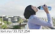 Купить «Side view of woman wearing hijab drinking outside », видеоролик № 33727254, снято 14 февраля 2020 г. (c) Wavebreak Media / Фотобанк Лори