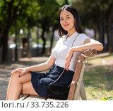Attractive brazilian girl sitting on a bench in summer park. Стоковое фото, фотограф Яков Филимонов / Фотобанк Лори