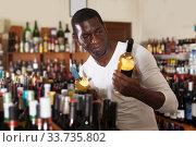 Afro man choosing bottle of wine. Стоковое фото, фотограф Яков Филимонов / Фотобанк Лори