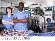 Купить «Two confident workers of dry cleaner», фото № 33735866, снято 15 января 2019 г. (c) Яков Филимонов / Фотобанк Лори