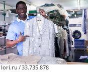 Купить «Worker of dry cleaner showing clean clothes», фото № 33735878, снято 15 января 2019 г. (c) Яков Филимонов / Фотобанк Лори