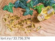 На деревянном фоне прозрачные желатиновые капсулы и флакон с рыбьим жиром. Омега-3 - незаменимые полиненасыщенные жирные кислоты. Стоковое фото, фотограф Наталья Гармашева / Фотобанк Лори