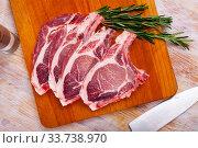Купить «Raw pork's chops and rosemary on wooden surface», фото № 33738970, снято 30 мая 2020 г. (c) Яков Филимонов / Фотобанк Лори