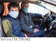 An elder father with teen age son wearing protective masks to prevent virus infection, sitting in car together, Finn people. Стоковое фото, фотограф Кекяляйнен Андрей / Фотобанк Лори