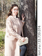 Smiling young woman wearing beige coat standing close to the tree in spring forest, holding book in hands. Стоковое фото, фотограф Кекяляйнен Андрей / Фотобанк Лори