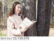 Joyful and calm Caucasian woman reads the book in spring forest, leaning the tree. Стоковое фото, фотограф Кекяляйнен Андрей / Фотобанк Лори