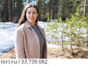 Attractive young woman wearing beige coat standing in spring forest against snow, portrait with copy space. Стоковое фото, фотограф Кекяляйнен Андрей / Фотобанк Лори