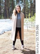 Full length portrait of attractive cheerful Caucasian woman walking in spring forest edge, long coat, sunny weather. Стоковое фото, фотограф Кекяляйнен Андрей / Фотобанк Лори
