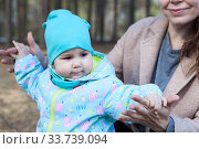 Toddler child stepping with mother support, female hands holding child, outdoor. Стоковое фото, фотограф Кекяляйнен Андрей / Фотобанк Лори