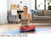 Купить «woman with smartphone sits on exercise mat at home», фото № 33739370, снято 25 марта 2020 г. (c) Syda Productions / Фотобанк Лори