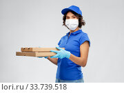 Купить «delivery woman in face mask with pizza boxes», фото № 33739518, снято 26 марта 2020 г. (c) Syda Productions / Фотобанк Лори