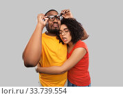 Купить «happy african american couple in glasses hugging», фото № 33739554, снято 15 декабря 2019 г. (c) Syda Productions / Фотобанк Лори