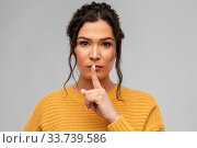 Купить «young woman with pierced nose making hush gesture», фото № 33739586, снято 20 марта 2020 г. (c) Syda Productions / Фотобанк Лори