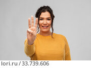 Купить «happy woman in pullover showing three fingers», фото № 33739606, снято 20 марта 2020 г. (c) Syda Productions / Фотобанк Лори