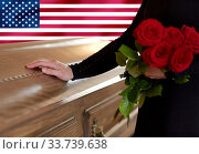 woman with red roses and coffin over american flag. Стоковое фото, фотограф Syda Productions / Фотобанк Лори