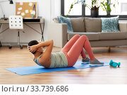 african woman doing abdominal exercises at home. Стоковое фото, фотограф Syda Productions / Фотобанк Лори