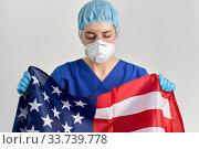 Купить «doctor in goggles and mask holding flag of america», фото № 33739778, снято 2 апреля 2020 г. (c) Syda Productions / Фотобанк Лори