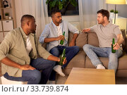 Купить «male friends drinking beer at home at night», фото № 33739874, снято 28 декабря 2019 г. (c) Syda Productions / Фотобанк Лори