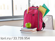 pink backpack, apple and school supplies on table. Стоковое фото, фотограф Syda Productions / Фотобанк Лори