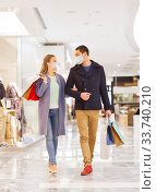 Купить «couple in medical masks with shopping bags in mall», фото № 33740210, снято 10 ноября 2014 г. (c) Syda Productions / Фотобанк Лори
