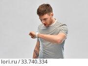 Купить «surprised young man looking at smart watch», фото № 33740334, снято 21 марта 2020 г. (c) Syda Productions / Фотобанк Лори