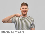 Купить «smiling man with toothpaste on wooden toothbrush», фото № 33740378, снято 21 марта 2020 г. (c) Syda Productions / Фотобанк Лори