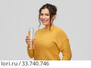 Купить «smiling young woman with water in glass bottle», фото № 33740746, снято 20 марта 2020 г. (c) Syda Productions / Фотобанк Лори