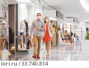 Купить «couple in medical masks with shopping bags in mall», фото № 33740814, снято 10 ноября 2014 г. (c) Syda Productions / Фотобанк Лори