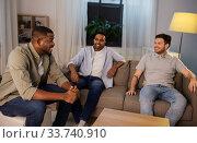Купить «happy male friends talking at home at night», фото № 33740910, снято 28 декабря 2019 г. (c) Syda Productions / Фотобанк Лори
