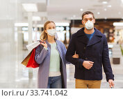 Купить «couple in medical masks with shopping bags in mall», фото № 33741042, снято 10 ноября 2014 г. (c) Syda Productions / Фотобанк Лори